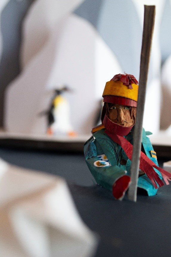 Karmenka is sat on a kayak in front of large mountain of ice: a glacier. She is wearing a helmet and thick, warm clothes. She is floating on a glacial river; behind her, a penguin runs across some ice.