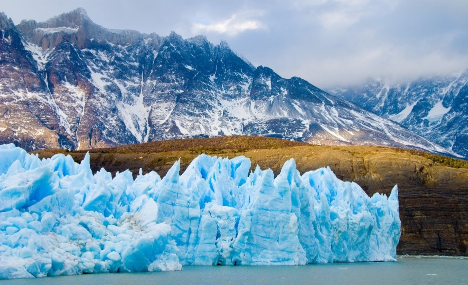 A glacier stretches across a river in front of some tall, sharp mountains. It's ice is blue and forms jagged peaks.
