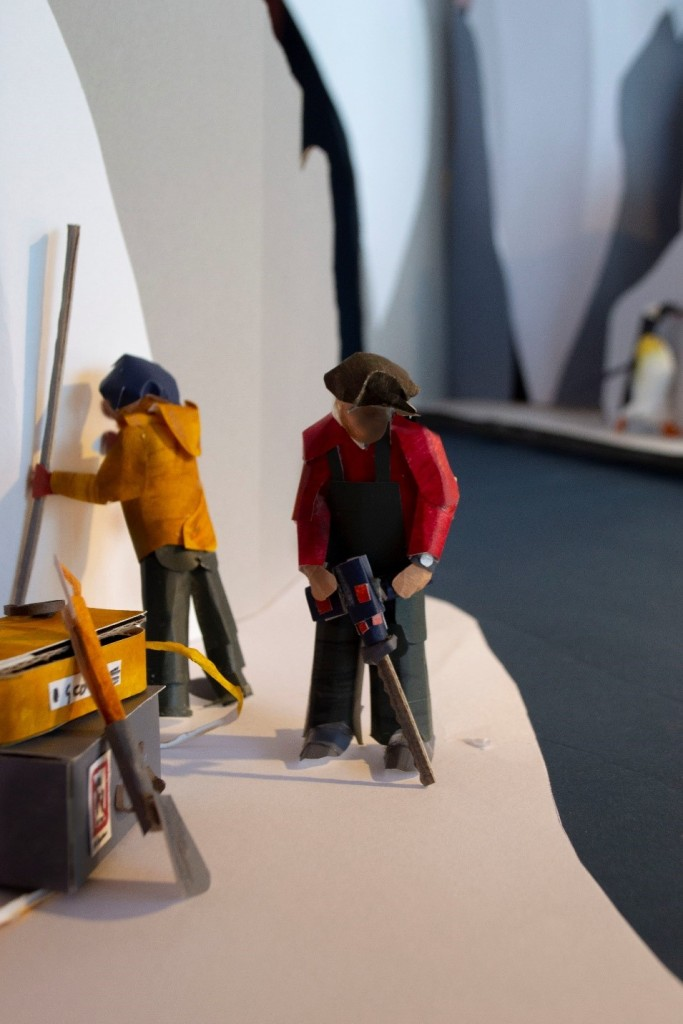 Two people are stood on ice. The glacier rises behind them. There is a stack of tool boxes beside them. One person is working with a long ice saw, while another is holding a large metal pole. They are hard at work.