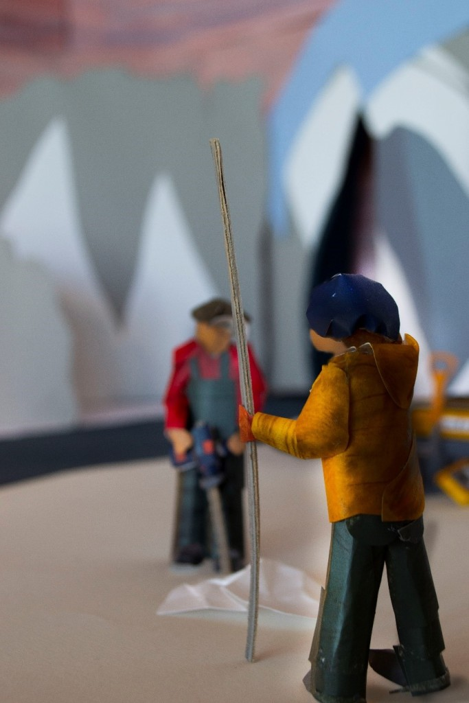 Two people are working on an ice floe in front of the glacier. One is holding a long metal pole, the other a drill. The pole is in focus - this is the part they are working on now.