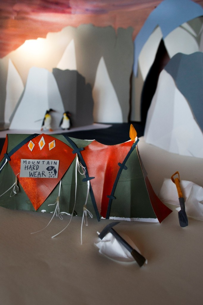 Karmenka's red and green tent is in focus. Behind it, the glacier rises, and penguins can be seen on the shore of the glacial river. An ice axe and shovel are left outside the tent; Karmenka will be back for them soon.