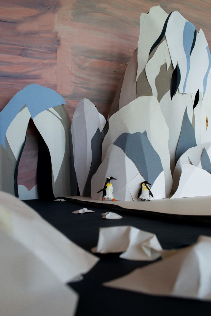 A view over the glacier landscape. In the glacial river, small ice floes move downstream. In the background, two penguins play. The rocks and ice rise up behind the river into mountain-like towers.