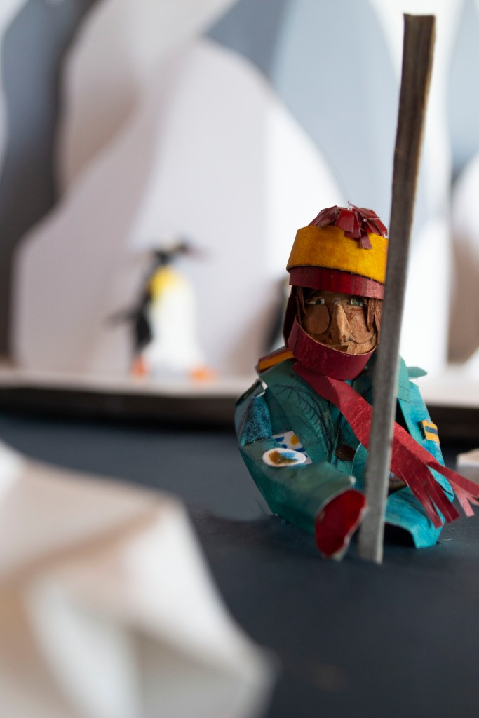 A kayaker made of paper is holding a long metal pole. They are in a river. In the background, a penguin can be seen, running past an icy mountain.